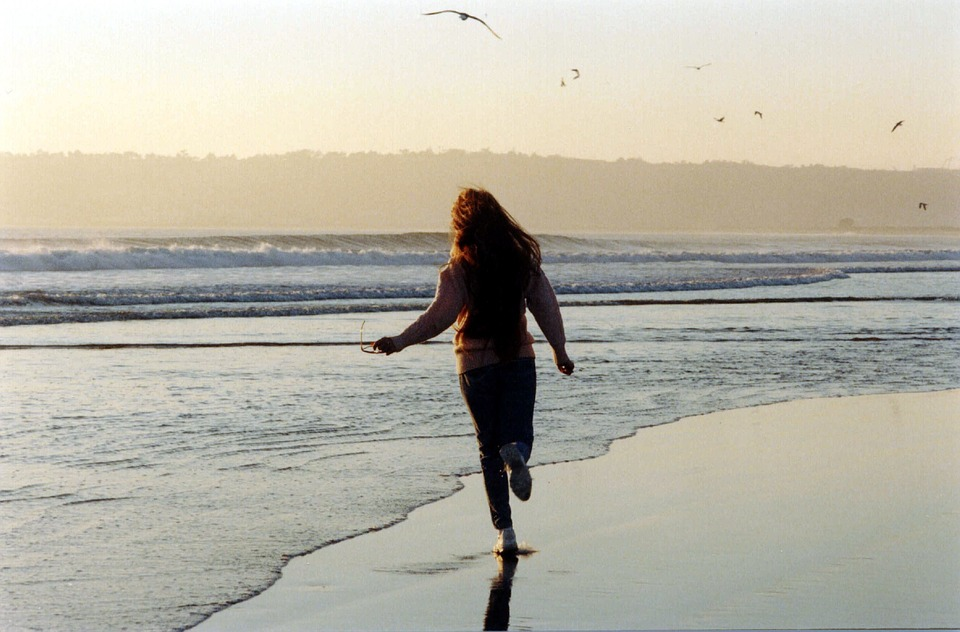 view of girl running, her back turned, along the beach. Point loma in background and the sun is setting with gentle yellow hues.