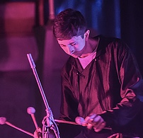 musician druming as he stands in soft purple and blue light