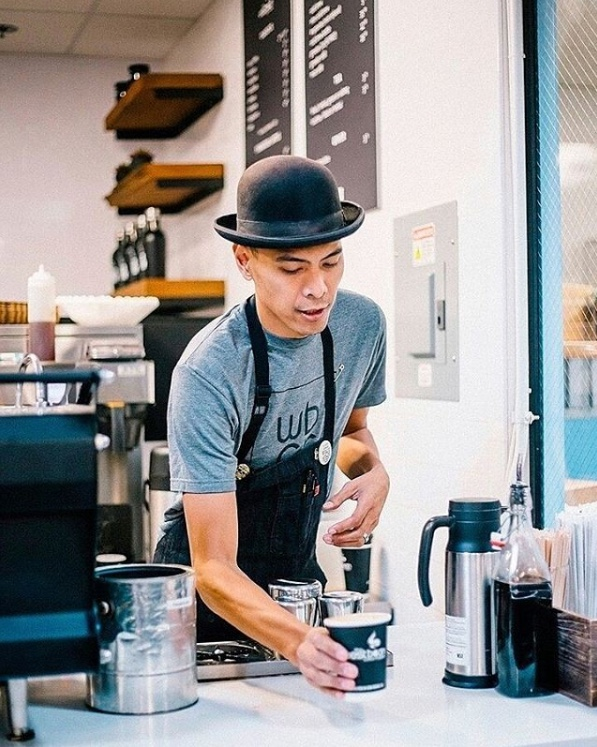 Barista with a bowlers hat serving coffee in a hipster looking cofeeshop