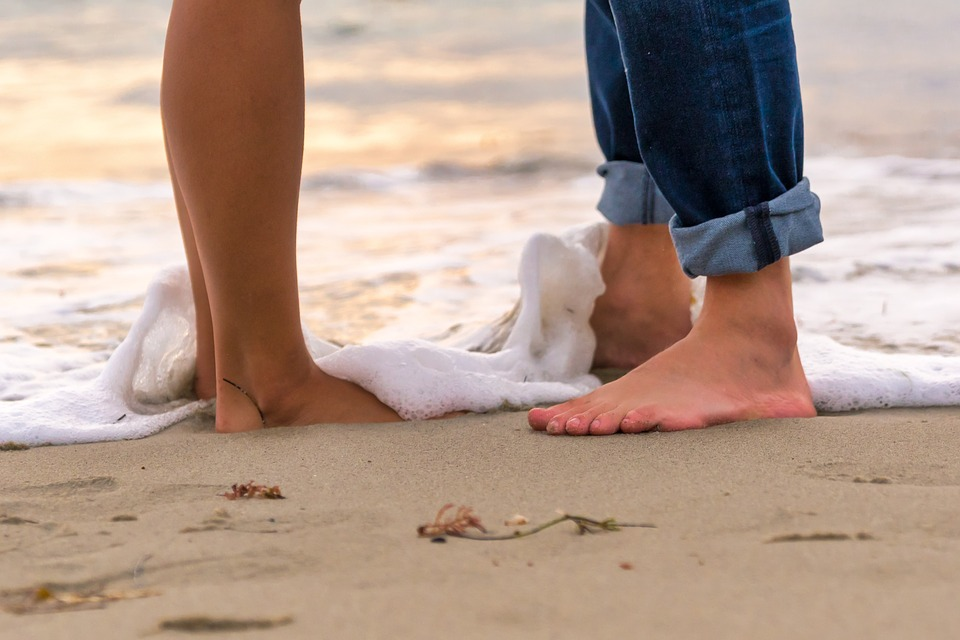 picture of two pair of feet, facing each other with gentle waves splashing on them