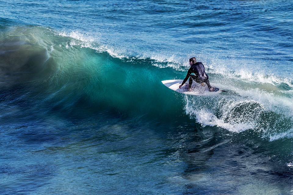 man surfing a wave in a wetsuite from right to left. The water is blue and emerald green, the sky is sunny